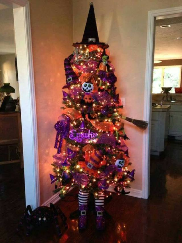 this designer used a black christmas tree and put orange and purple netting on it they also added fun halloween ornaments - Black Christmas Tree With Purple Decorations